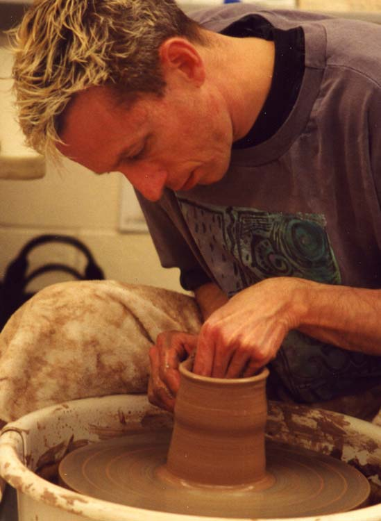 Rick Hoffman makes a clay cylinder on the pottery wheel